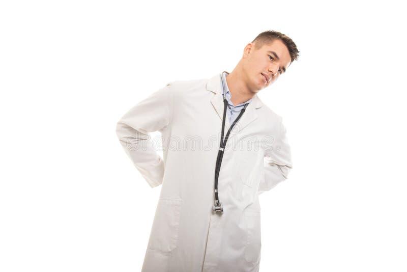 Stående av den unga stiliga doktorn som rymmer lägre baksida som att göra ont arkivfoto