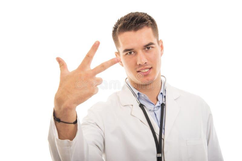 Stående av den unga stiliga doktorn som visar gest för nummer tre royaltyfria foton