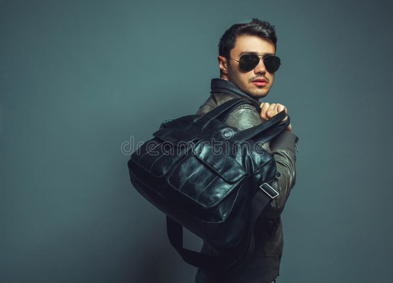 Stående av den unga stiliga fasionmannen med läderpåsen som bär s fotografering för bildbyråer