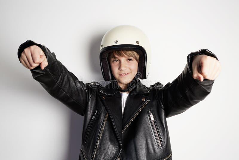 Stående av den unga stiliga gladlynta tonåriga pojken i svart läderomslag och den vita motohjälmen som låtsar för att rida a royaltyfri bild