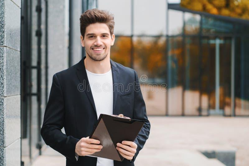 Stående av den unga stiliga mannen i omslag med dokument, nytto- räkningar, rapport Affärsman nära kontorsbyggnad Han är arkivfoto