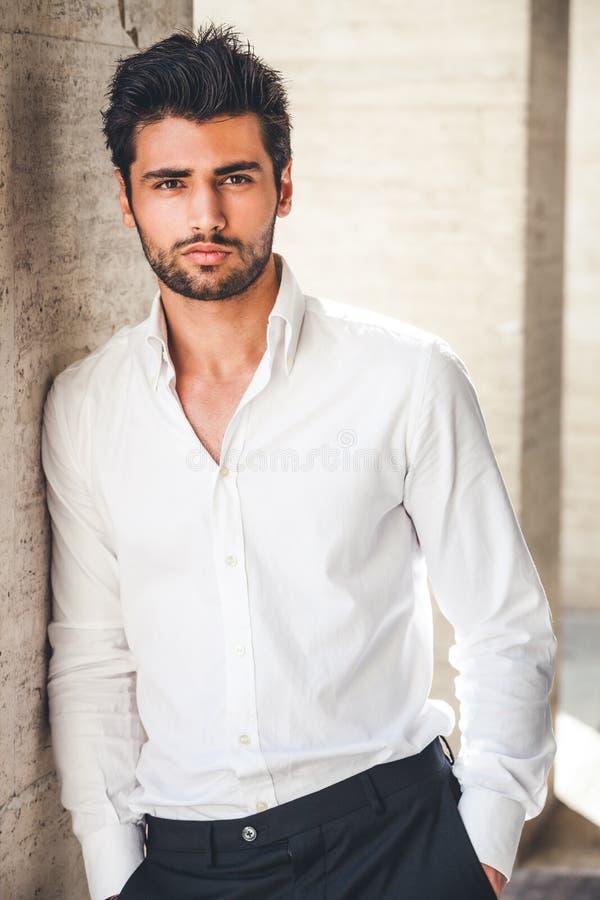 Stående av den unga stiliga mannen i den utomhus- vita skjortan royaltyfria foton