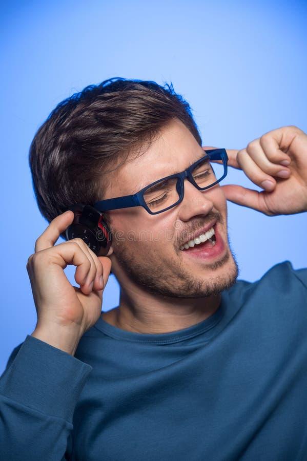 Stående av den unga stiliga mannen med hörlurar arkivbilder