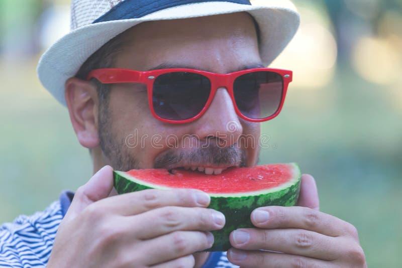 Stående av den unga stiliga mannen som äter vattenmelon, hållande vattenmelon för man royaltyfria foton