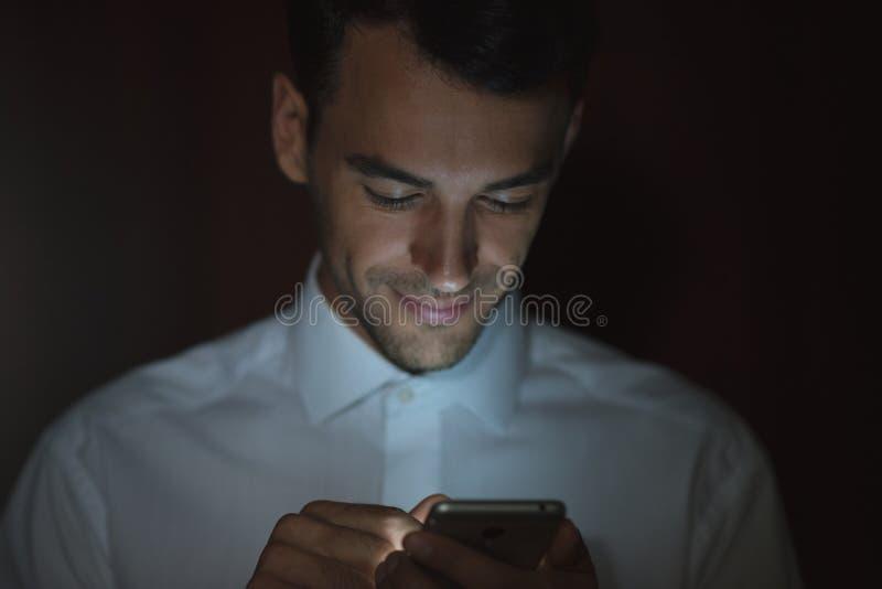 Stående av den unga stiliga mannen som använder den smarta telefonen i hand på mörk bakgrund arkivfoton