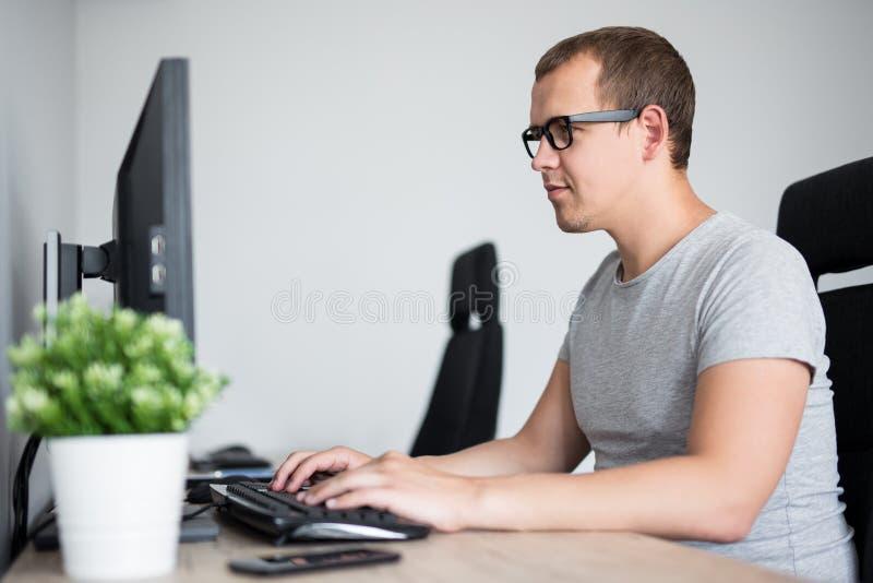 Stående av den unga stiliga mannen som i regeringsställning eller hem använder datoren arkivfoton