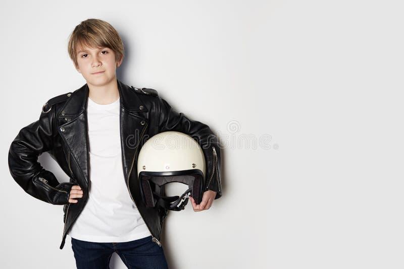 Stående av den unga stiliga tonåriga pojken i svart omslag och att rymma för läder den vita motohjälmen för hand som ler på vit arkivbilder