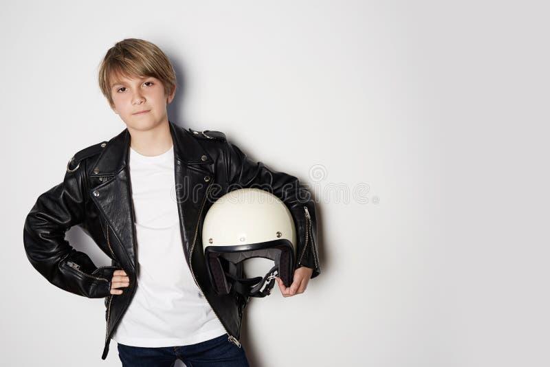 Stående av den unga stiliga tonåriga ungen i svart omslag och att rymma för läder den vita motohjälmen för hand som ler på vit royaltyfri fotografi