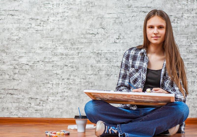 Stående av den unga tonåringbrunettflickan med långt hår som sitter på golv och drar bilden på grå väggbakgrund fotografering för bildbyråer