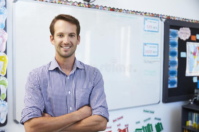 Stående av den unga vita manliga läraren i skolaklassrum royaltyfri foto
