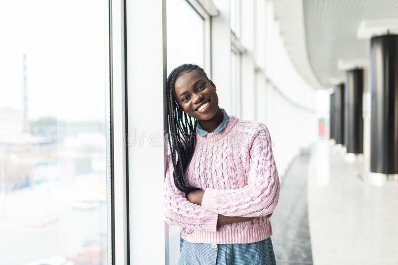 Stående av den unga yrkesmässiga härliga säkra kvinnan som ler nära exponeringsglasfönstret, isolerad inomhus kontorsbakgrund pos arkivfoton