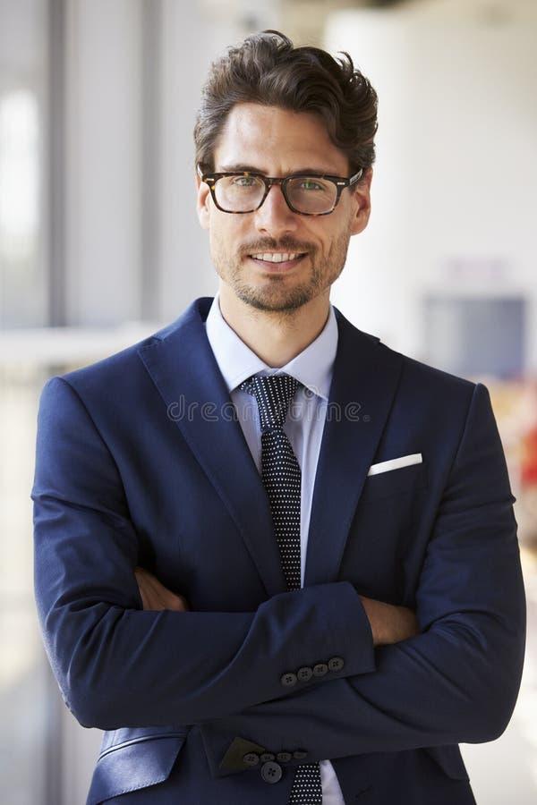 Stående av den unga yrkesmässiga mannen i dräkten, korsade armar arkivbilder