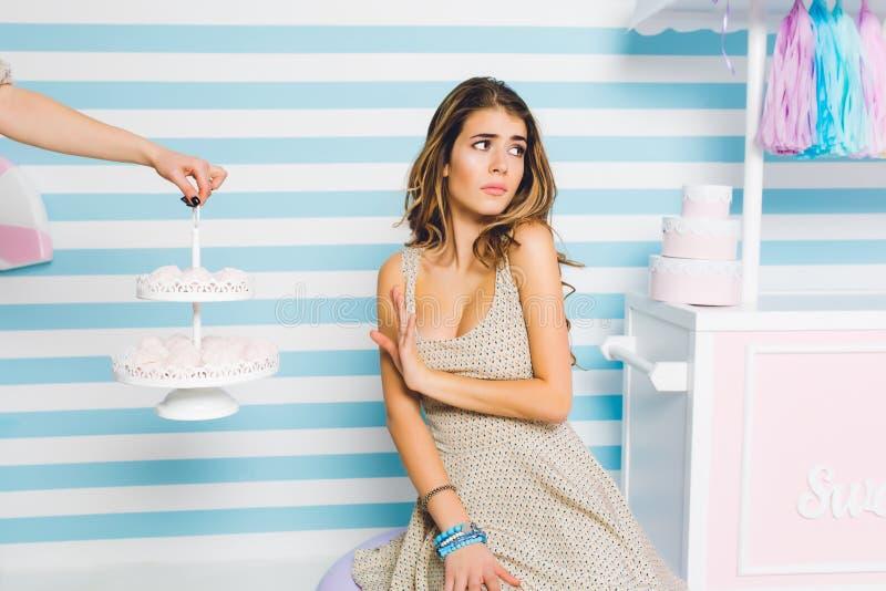 Stående av den unpleased vänden för ung kvinna i väg från smakliga kakor som poserar på gullig randig bakgrund Elegant flicka i m royaltyfria foton