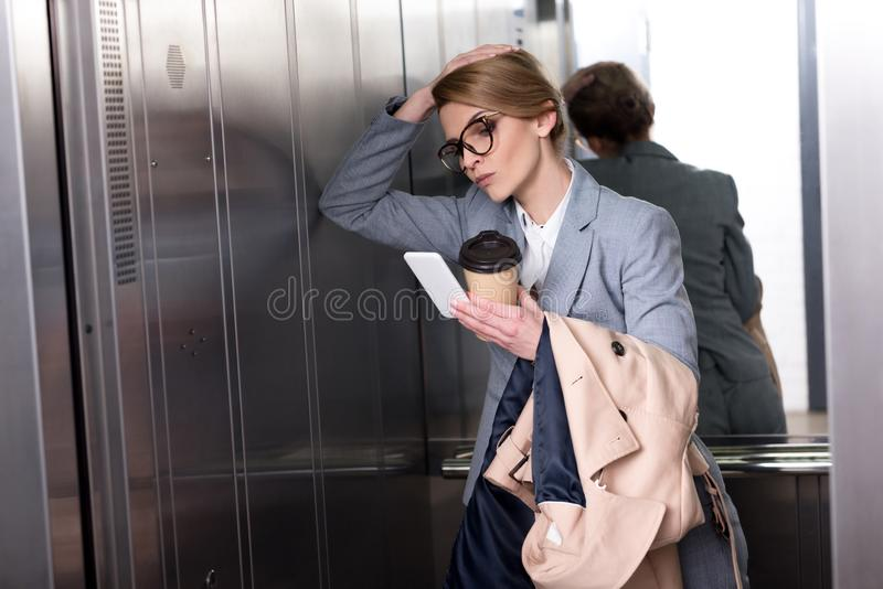 stående av den unsatisfied affärskvinnan i dräkt med smartphonen arkivbilder
