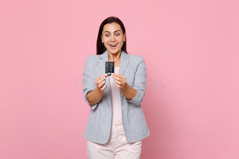 Stående av den upphetsade förvånade unga kvinnan i det randiga omslaget som rymmer krediteringskontokortet isolerad på den rosa p royaltyfri foto