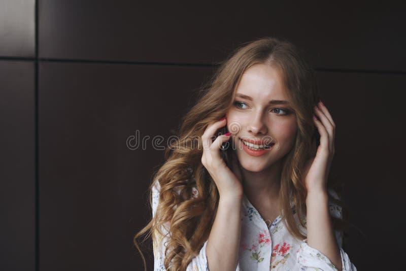 Stående av den upphetsade härliga flickan som ser mobiltelefonen och royaltyfria foton