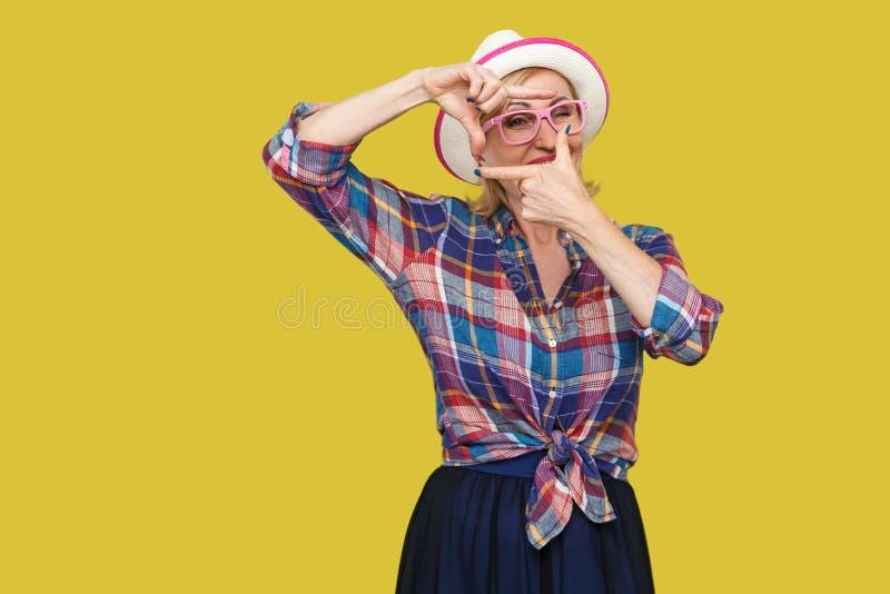 Stående av den uppmärksamma moderna stilfulla mogna kvinnan i tillfällig stil med hatten och glasögon som står med skördsammansät arkivbild