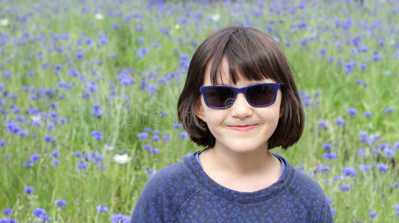 Stående av den uppnosiga ungen med solglasögon för glädje och barndom arkivfoto
