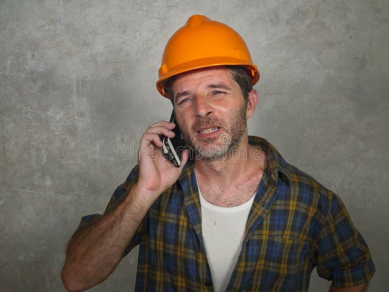 Stående av den upprivna byggnadsarbetaren eller den stressade leverantörmannen i byggmästarehatt som talar på mobiltelefonen som  arkivfoton