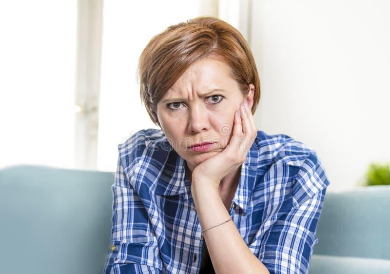 Stående av den upprivna och nätta röda hårkvinnan omkring 30 år gammal hemmastadd vardagsrum som ser ledsen och bekymrad i sorgse fotografering för bildbyråer