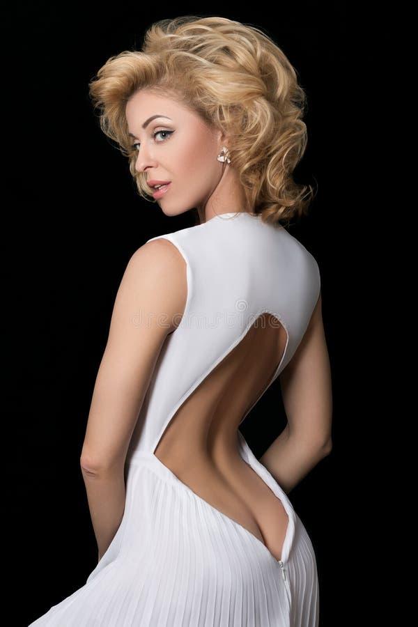 Stående av den ursnygga mogna blonda kvinnan i den vita klänningen royaltyfria foton