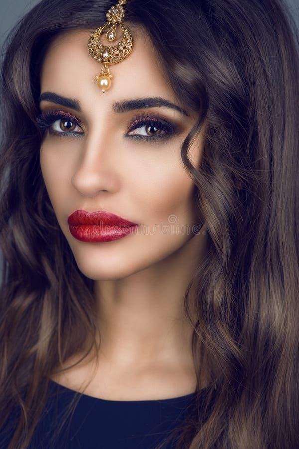 Stående av den ursnygga unga brunetten med långt hår och provokativa sminket som bär dyrbar indisk brud- hårtillbehör arkivbilder