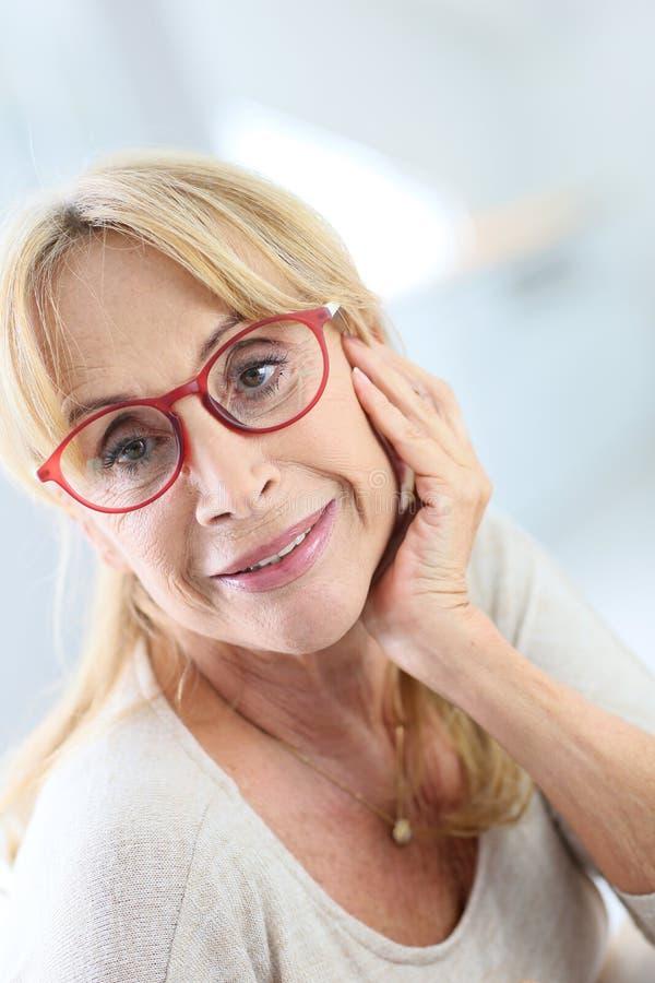 Stående av den utsmyckade höga kvinnan med rött glasögon arkivfoto