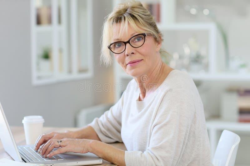 Stående av den utsmyckade höga kvinnan på bärbara datorn royaltyfri foto