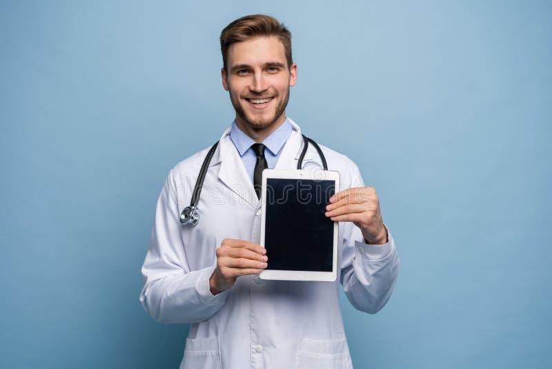 Stående av den vänliga doktorn som framlägger den tomma digitala minnestavlaskärmen Isolerat på ljust - blått royaltyfri fotografi