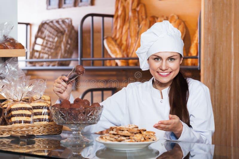 Stående av den vänliga unga kvinnan på bageriskärm med bakelse arkivfoton