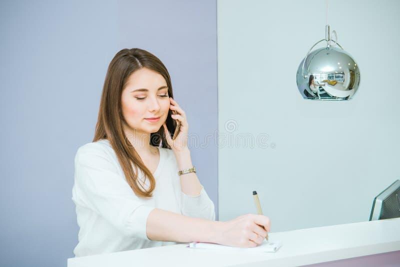 Stående av den vänliga unga kvinnan som talar på telefonen och gör anmärkningen bak mottagandeskrivbordet Administratör i kontore arkivfoton