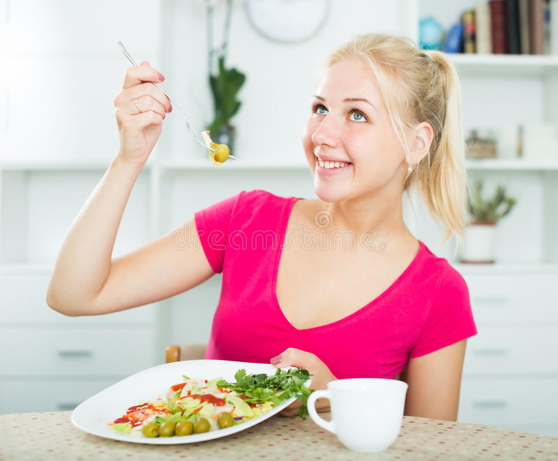 Stående av den vuxna blonda flickan som äter sallad arkivbild