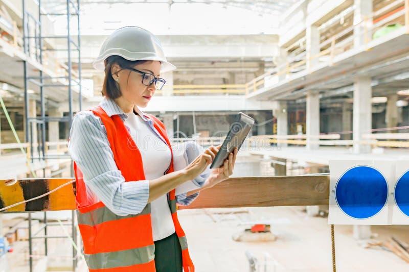 Stående av den vuxna kvinnliga byggmästaren, tekniker, arkitekt, inspektör, chef på konstruktionsplatsen Kvinna med plan, digital royaltyfri foto