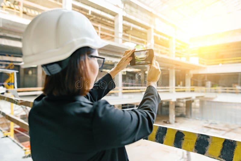 Stående av den vuxna kvinnliga byggmästaren, tekniker, arkitekt, inspektör, chef på konstruktionsplatsen Kvinnan gör fotoet av by royaltyfri bild
