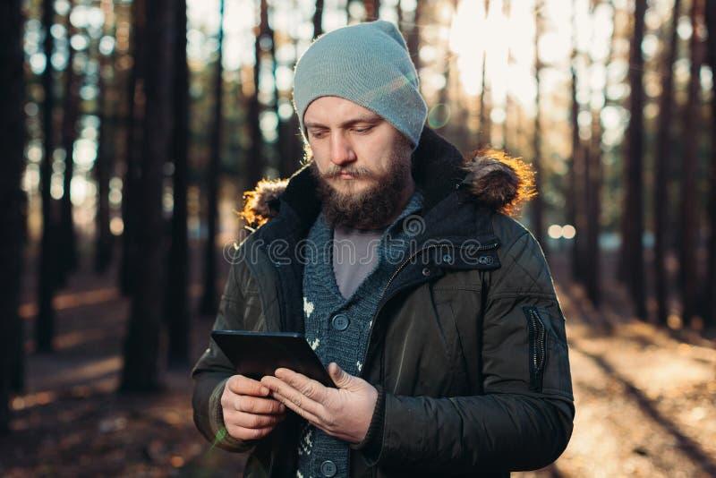 Stående av den vuxna mannen som går i pinjeskogen med den digitala minnestavlan royaltyfri fotografi