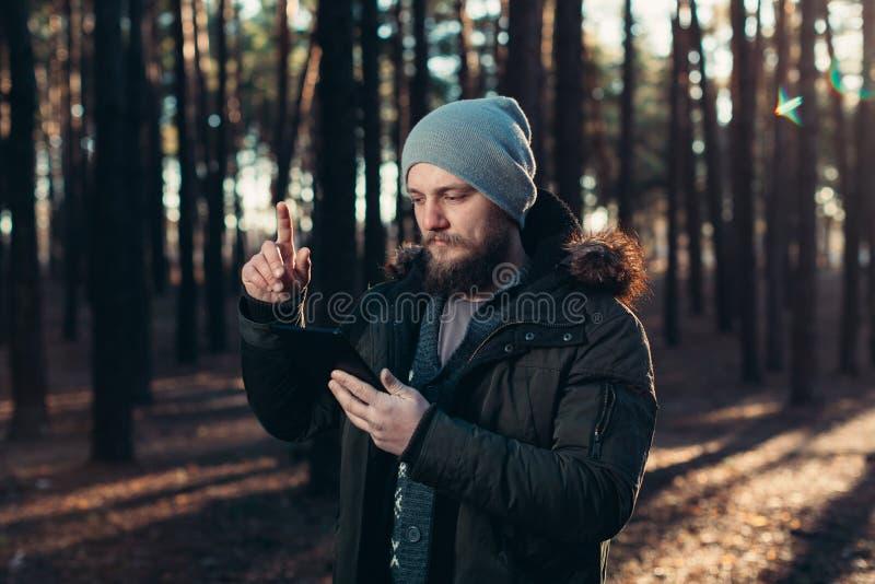 Stående av den vuxna mannen som går i pinjeskogen med den digitala minnestavlan arkivfoton