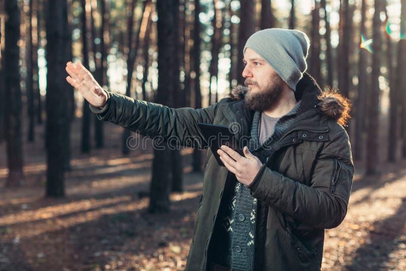 Stående av den vuxna mannen som går i pinjeskogen med den digitala minnestavlan royaltyfri foto