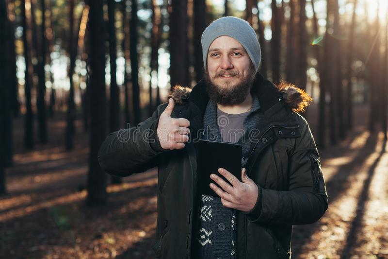 Stående av den vuxna mannen som går i pinjeskogen med den digitala minnestavlan royaltyfria bilder