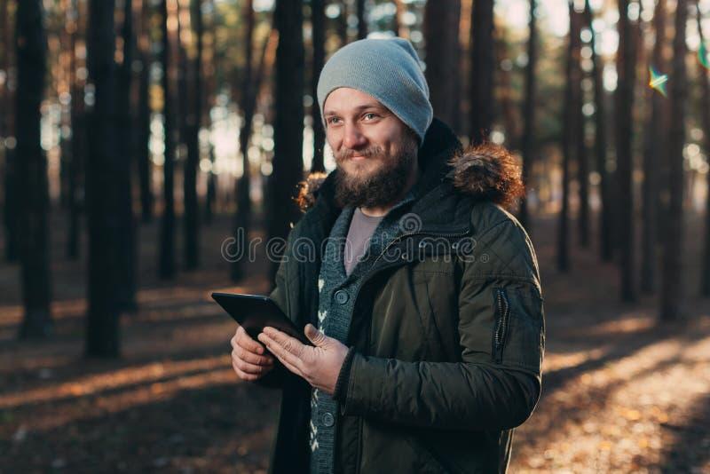 Stående av den vuxna mannen som går i pinjeskogen med den digitala minnestavlan arkivbilder