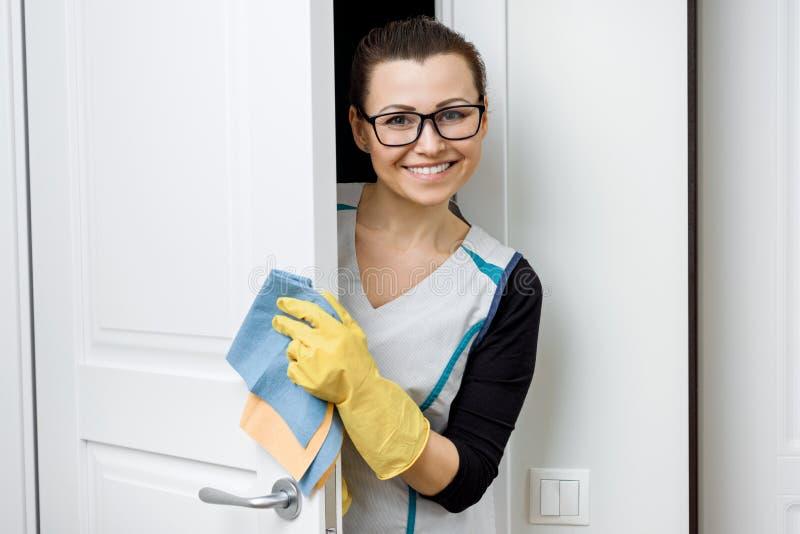 Stående av den vuxna positiva le kvinnan i exponeringsglas och förklädet för rengörande gummihandskar med tvättmedel, vit dörrbak royaltyfria foton