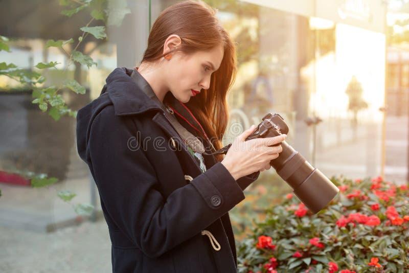 Stående av den yrkesmässiga kvinnliga fotografen på gatan som fotograferar på en kamera royaltyfria foton
