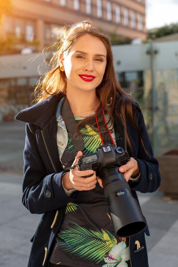 Stående av den yrkesmässiga kvinnliga fotografen på gatan som fotograferar på en kamera royaltyfri fotografi