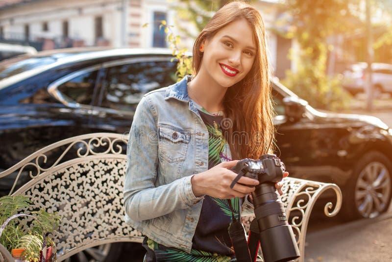 Stående av den yrkesmässiga kvinnliga fotografen på gatan som fotograferar på en kamera royaltyfri bild