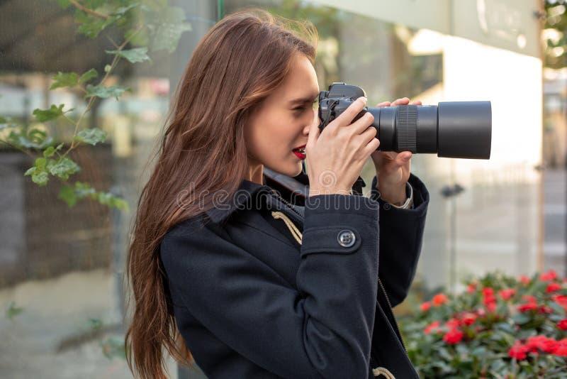 Stående av den yrkesmässiga kvinnliga fotografen på gatan som fotograferar på en kamera royaltyfri foto