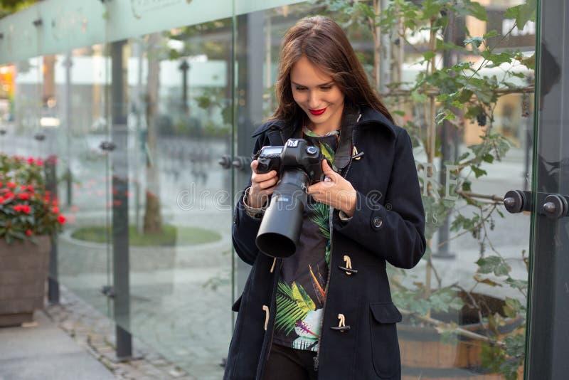 Stående av den yrkesmässiga kvinnliga fotografen på gatan som fotograferar på en kamera royaltyfria bilder