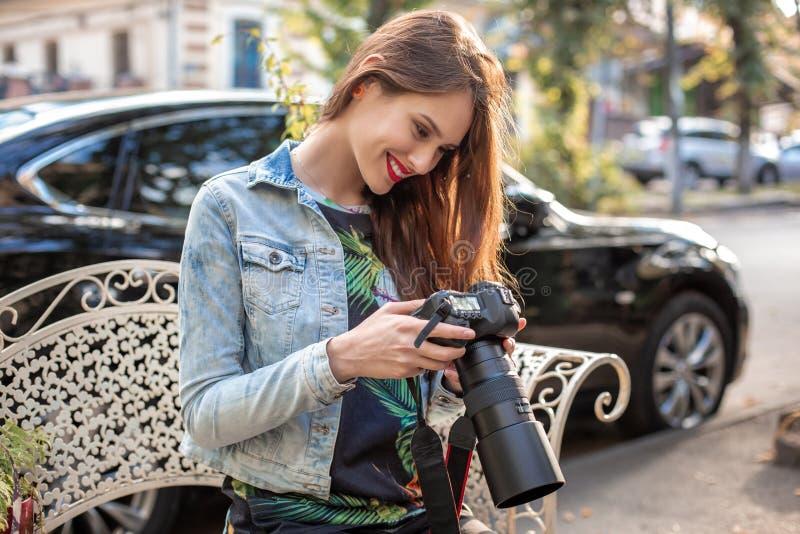 Stående av den yrkesmässiga kvinnliga fotografen på gatan som fotograferar på en kamera arkivfoto