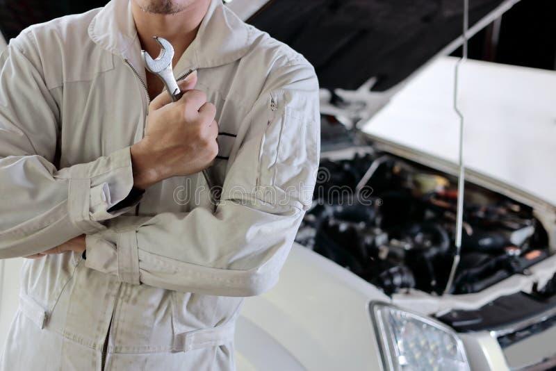 Stående av den yrkesmässiga unga mekanikermannen i enhetlig innehavskiftnyckel mot bilen i öppen huv på reparationsgaraget fotografering för bildbyråer