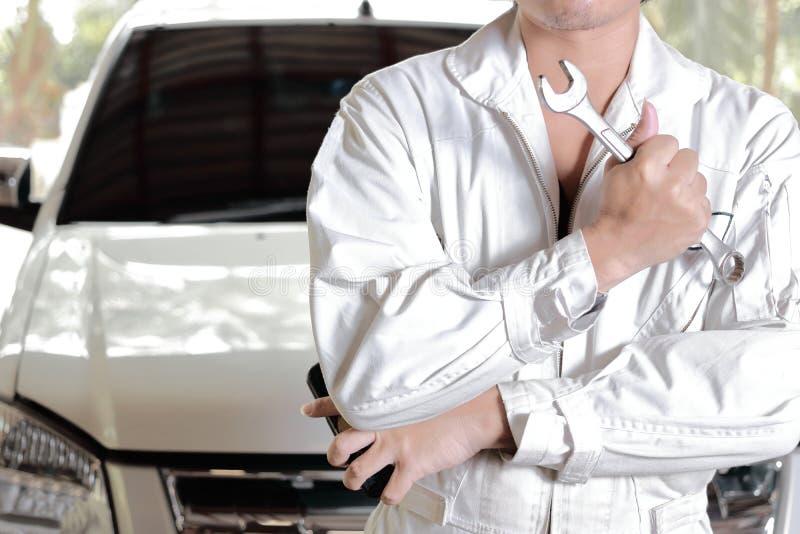Stående av den yrkesmässiga unga mekanikermannen i enhetlig innehavskiftnyckel mot bilen i öppen huv på reparationsgaraget arkivfoto