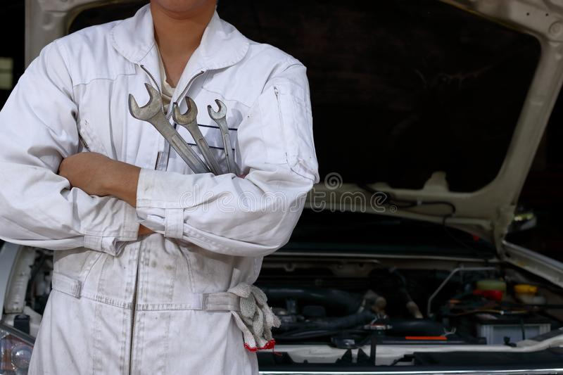 Stående av den yrkesmässiga unga mekanikermannen i enhetlig innehavskiftnyckel mot bilen i öppen huv på reparationsgaraget royaltyfri foto