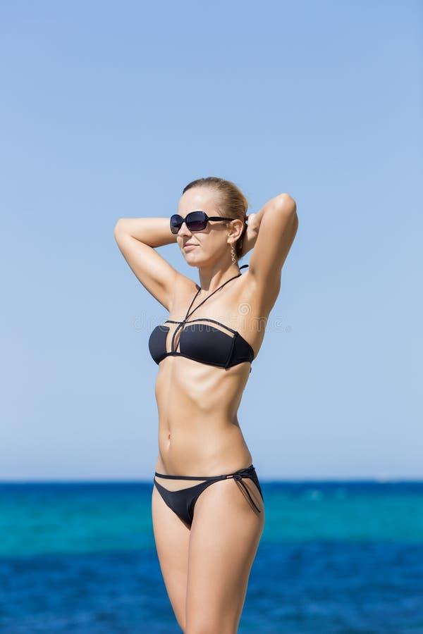 Stående av denhaired flickan i svart baddräkt mot havet arkivfoto